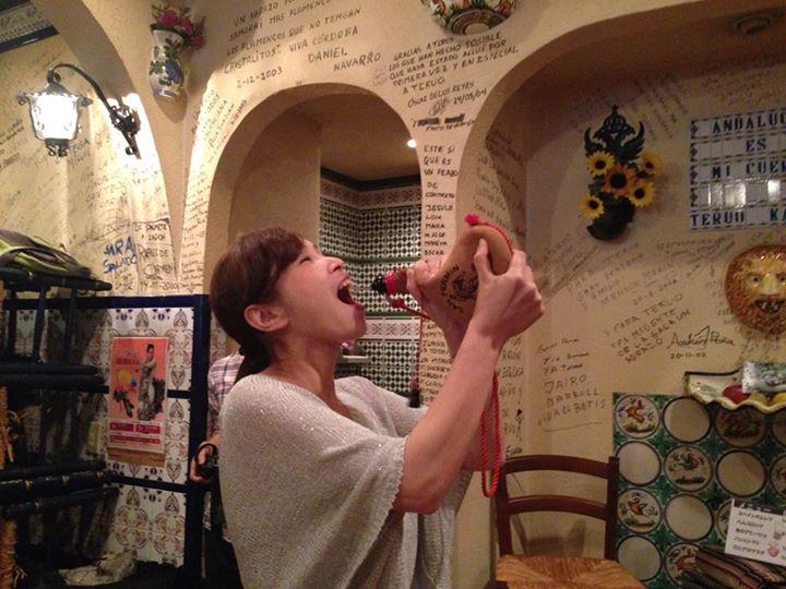 Turista japonesa echando un trago de vino a una bota