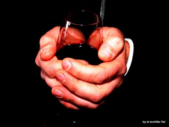 Manos calentando vino