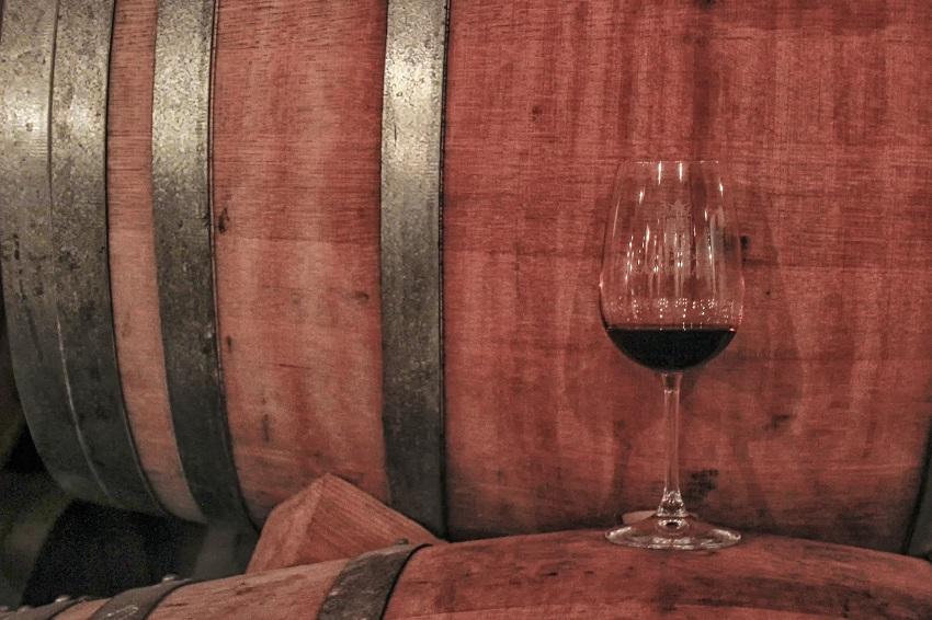 barrica junto a copa de vino tinto
