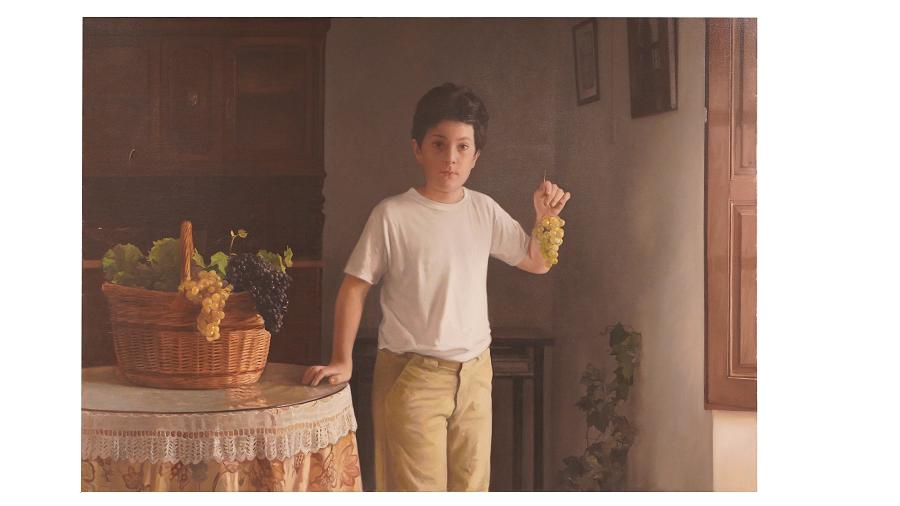 Niño sujeta con su mano un racimo de uvas. Mira atentamente al espectador.