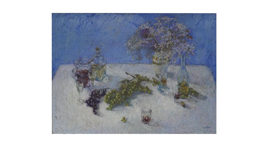 Uvas sobre la mesa al lado de un florero repleto de flores. También vemos un vasito con un poco de vino.