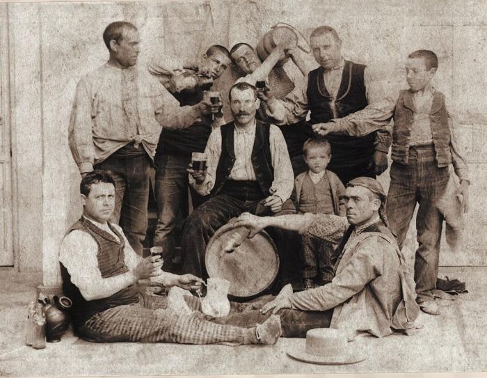 Grupo de hombres disfrutan con entusiasmo del vino.